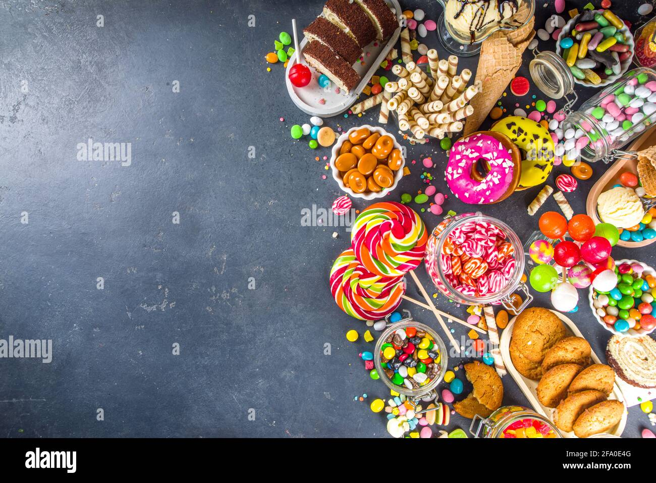 Selection of colorful sweets. Set of various candies, chocolates, donuts, cookies, lollipops, ice cream top view on black concrete background Stock Photo