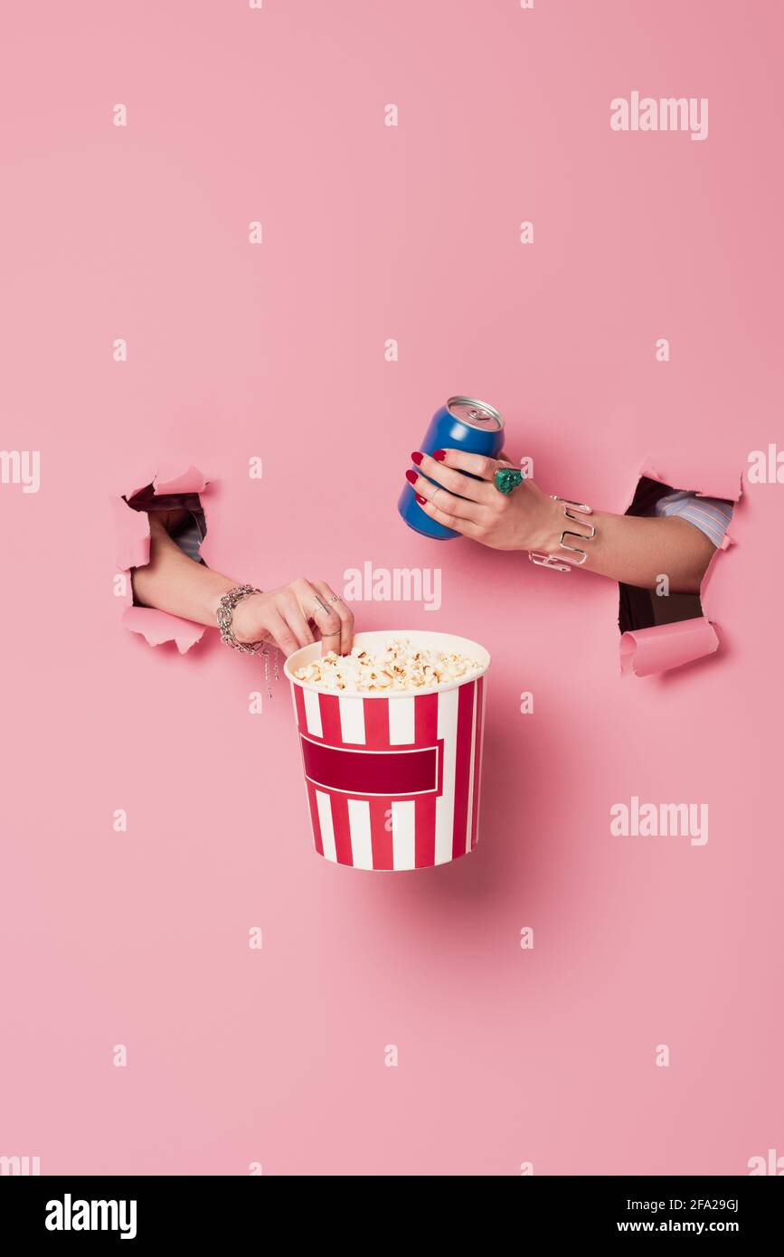 Cropped view of woman holding popcorn and drink in can near pink background with holes Stock Photo