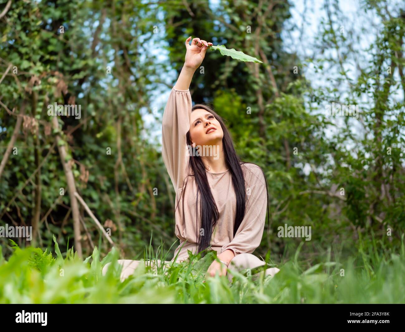 Young woman in nature hand holding single leaf high above head looking up upwards against sky sitting low view in vegetation in forest amongst trees Stock Photo