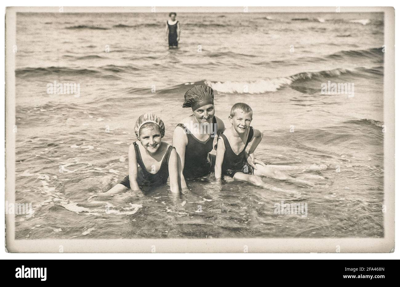 Old photo mother and kids on the sea. Summer holidays vacation. Vintage picture with original film grain and blur from ca. 1920 Stock Photo