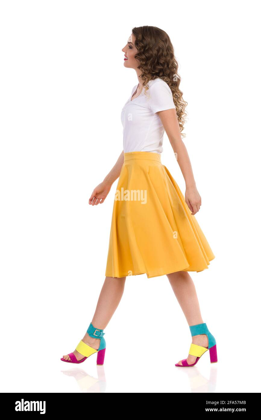 Beautiful young woman in white top, yellow skirt and colorful high heels is walking and looking away. Side view. Full length studio shot isolated on w Stock Photo