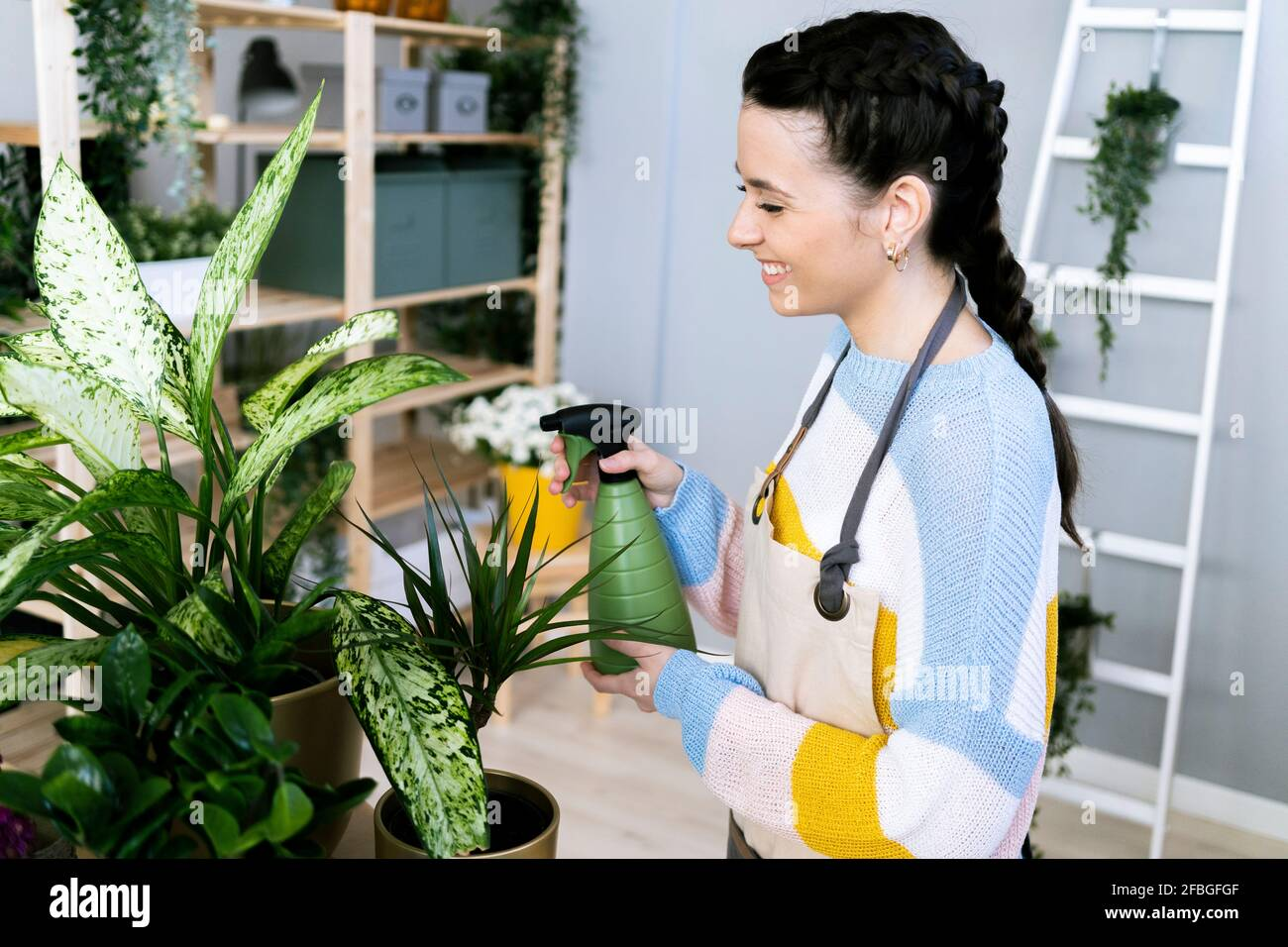 Smiling woman spraying water on plants while working at workshop Stock Photo