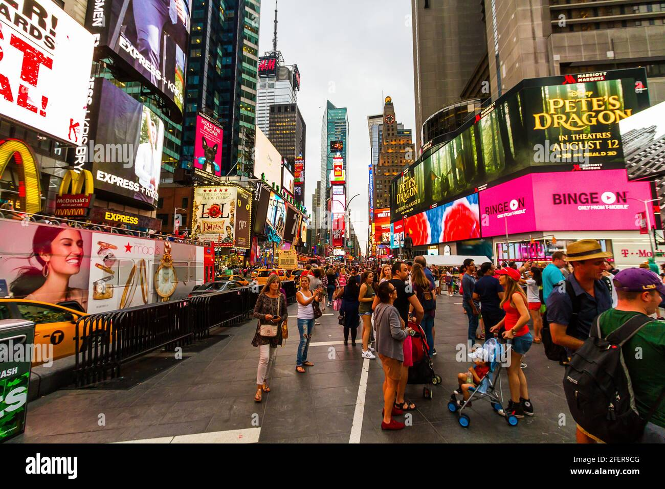 Tourist in summer outfits taking photos at Times Square on a busy evening Stock Photo