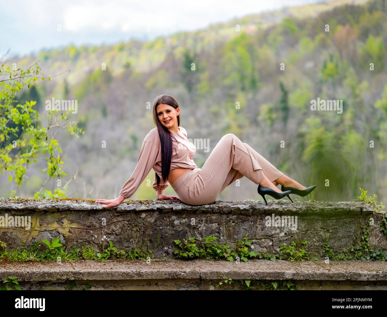 Strike pose on edge of stone wall smiling happy young woman stiletto heels Stock Photo