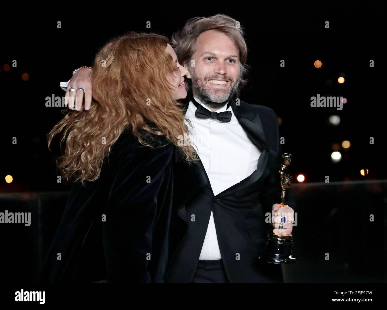 """Florian Zeller embraces Marine Delterme as he holds his Oscars statuette after winning the Best Adapted Screenplay for the """"The Father"""" at a screening of the Oscars in Paris, France April 26, 2021. Lewis Joly/Pool via REUTERS Stock Photo"""