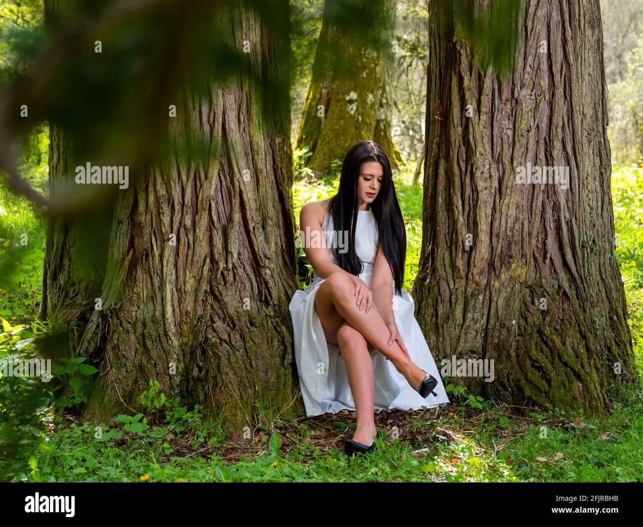 Leg pain painful young woman crossed legs cross legged heels Stock Photo