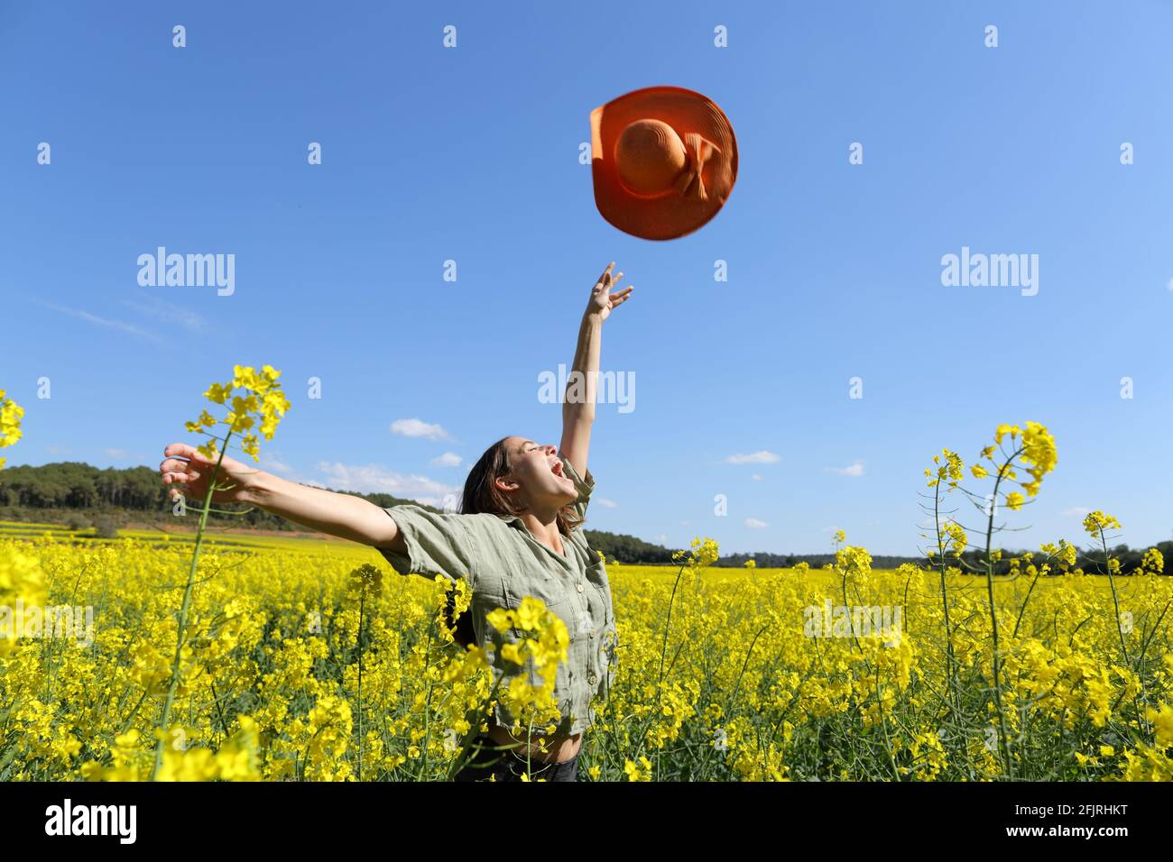 Happy woman throwing pamela celebrating vacation in a yellow flowered field in spring Stock Photo