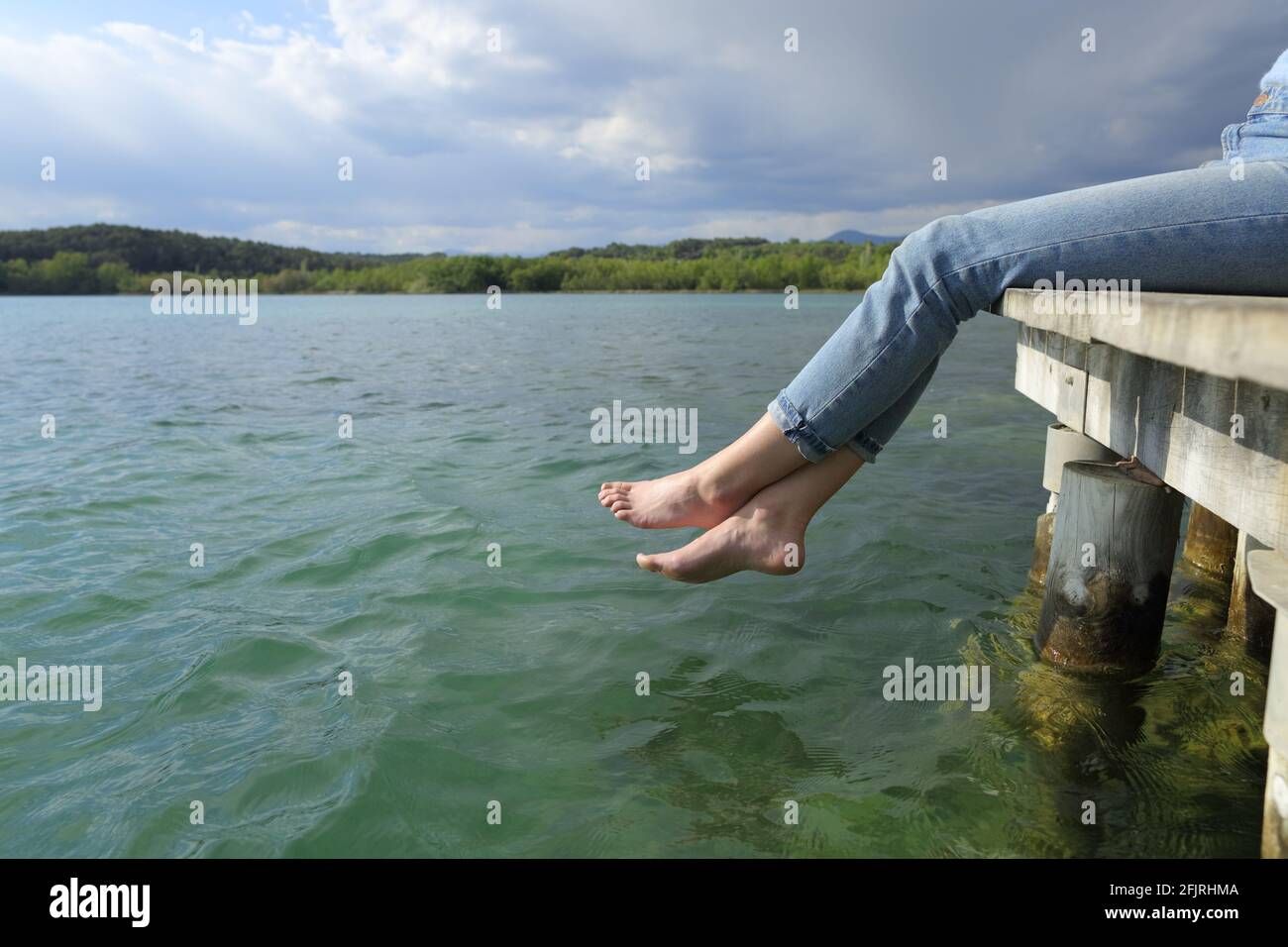 Side view close up of a woman legs and feet resting sitting in a lake pier Stock Photo