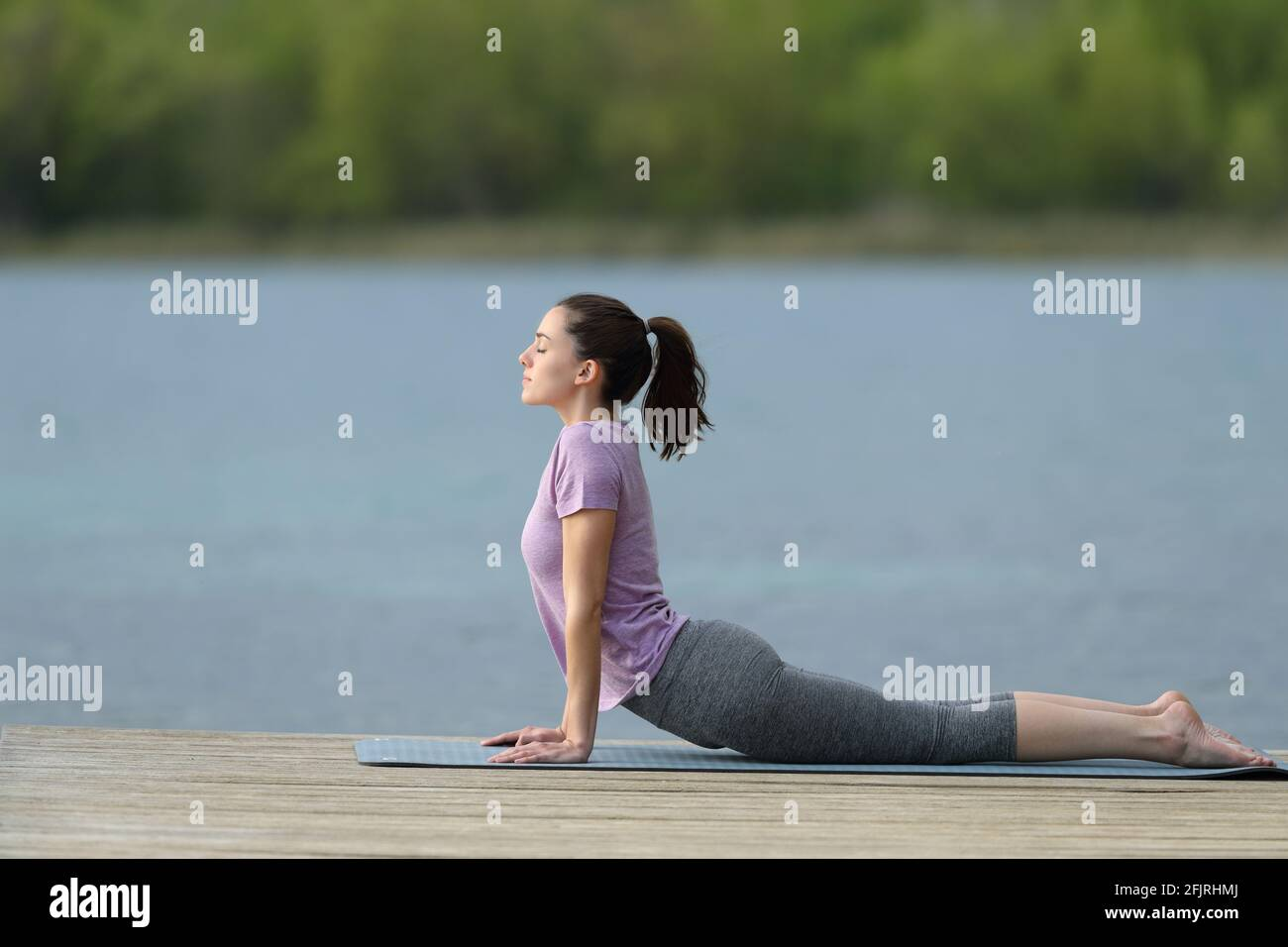 Profile of a woman doing yoga pose in a lake pier on summer Stock Photo