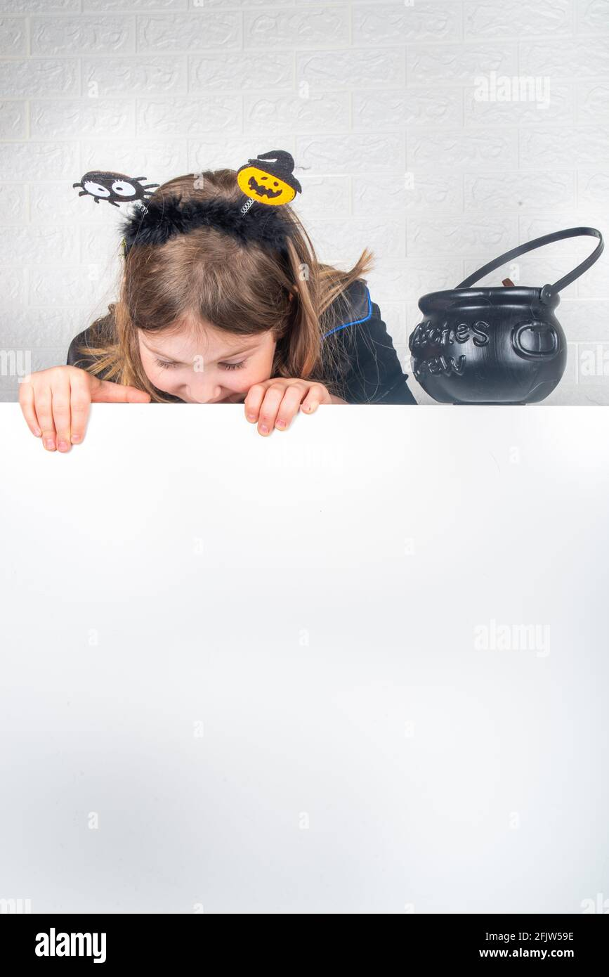 Autumn holiday Halloween invitation, greeting card background. Happy Caucasian child girl in a dress and a witch hat, with buckets of sweets copy spac Stock Photo