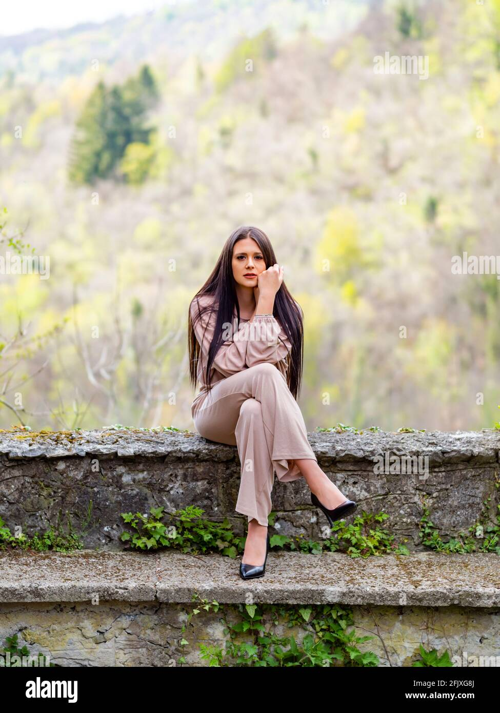 Young woman crossed legs cross legged heels Stock Photo