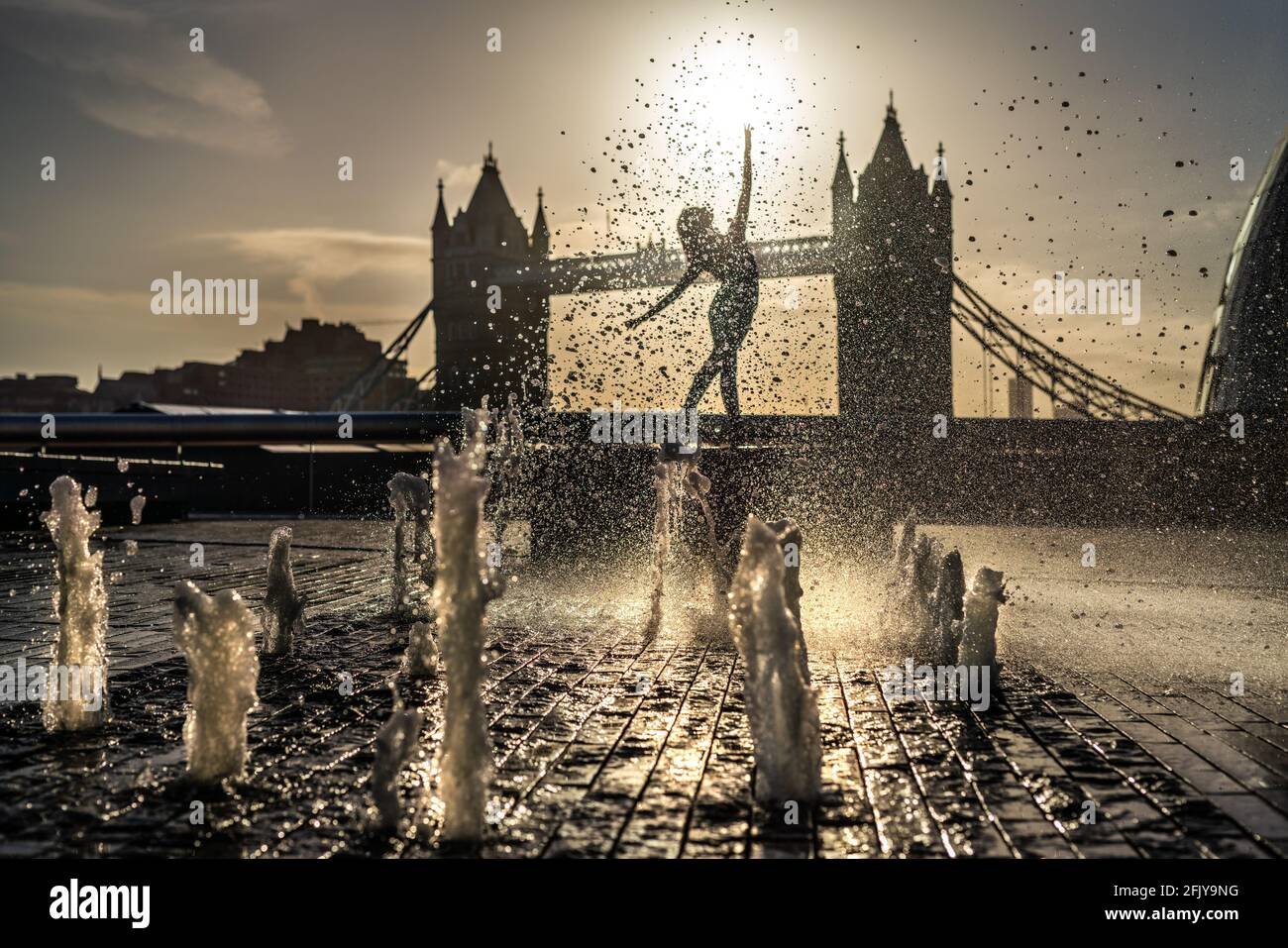 London, UK. 27th April 2021. International Dance Day: Rebecca Olarescu, a Masters screendance student at the London Contemporary Dance School (LCDS), performs during a dramatic sunrise at the fountains near Tower Bridge ahead of International Dance Day on 29th April. First celebrated in 1982, International Dance Day has taken place every year since in anniversary celebration of the birth of Jean-Georges Noverre (1727-1810), the creator of modern ballet. Credit: Guy Corbishley/Alamy Live News Stock Photo