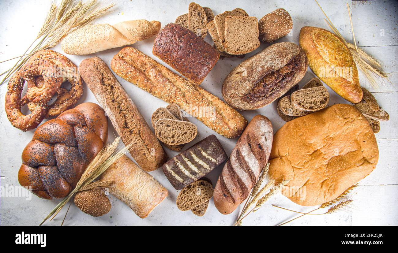 Assortment of various delicious freshly baked bread, on white background top view copy space Stock Photo