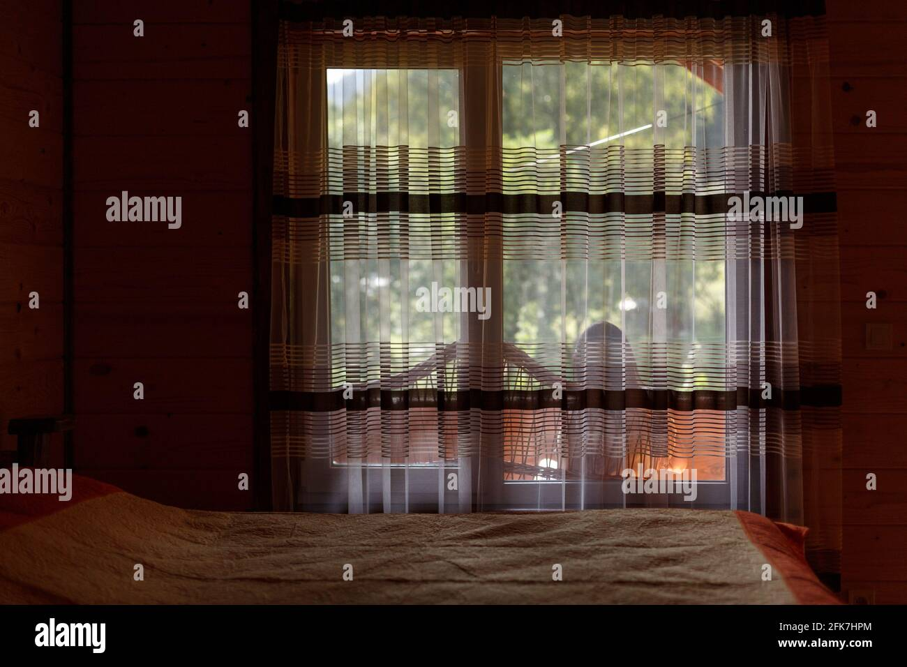Relaxation and rest. Large window by the bed in the guest room of the wooden cottage. Girl is sitting on the terrace outside the window and enjoying h Stock Photo