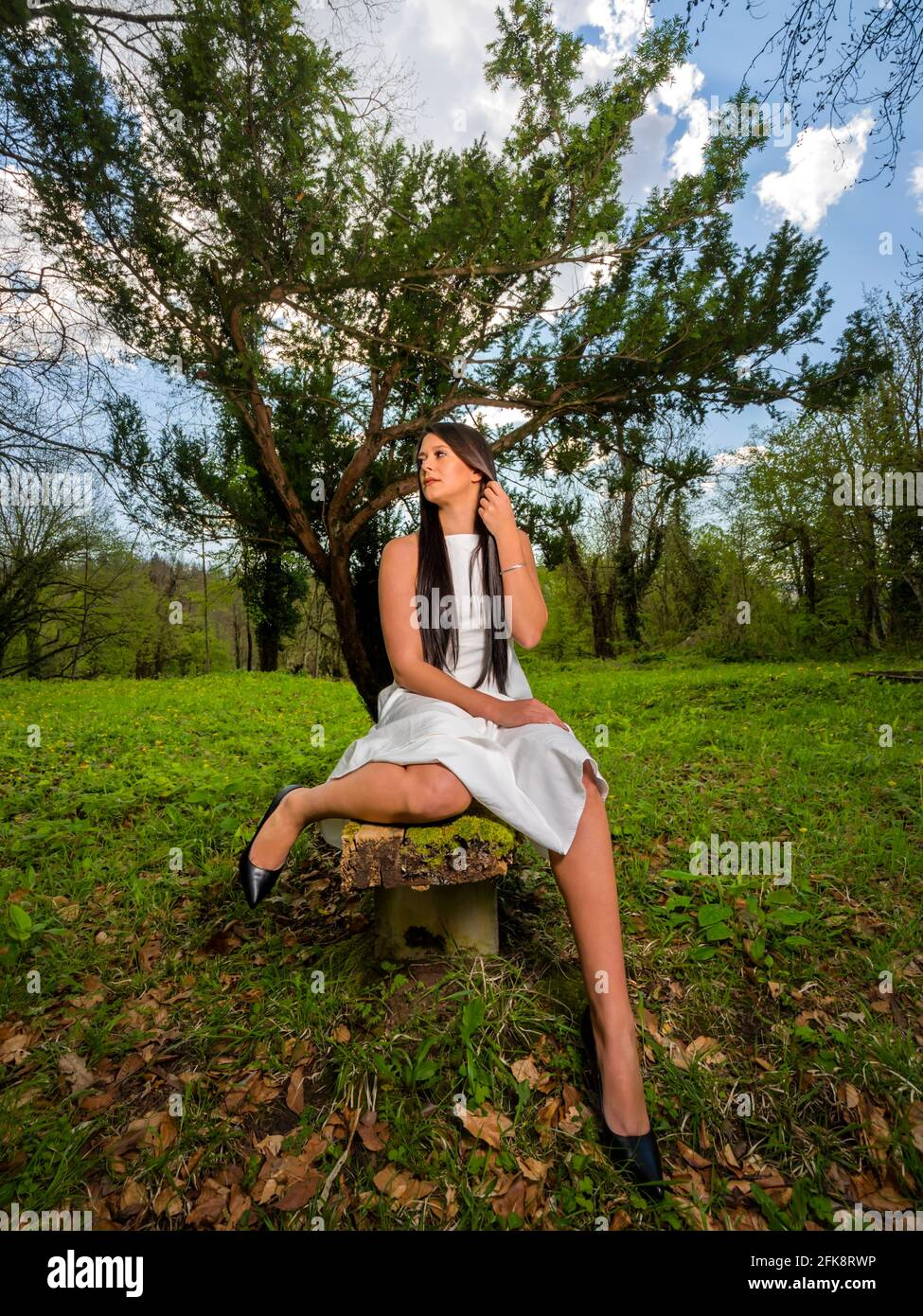 Young woman sitting on wooden bench awkward in park looking aside sad away wearing White dress legs high-heels Stock Photo