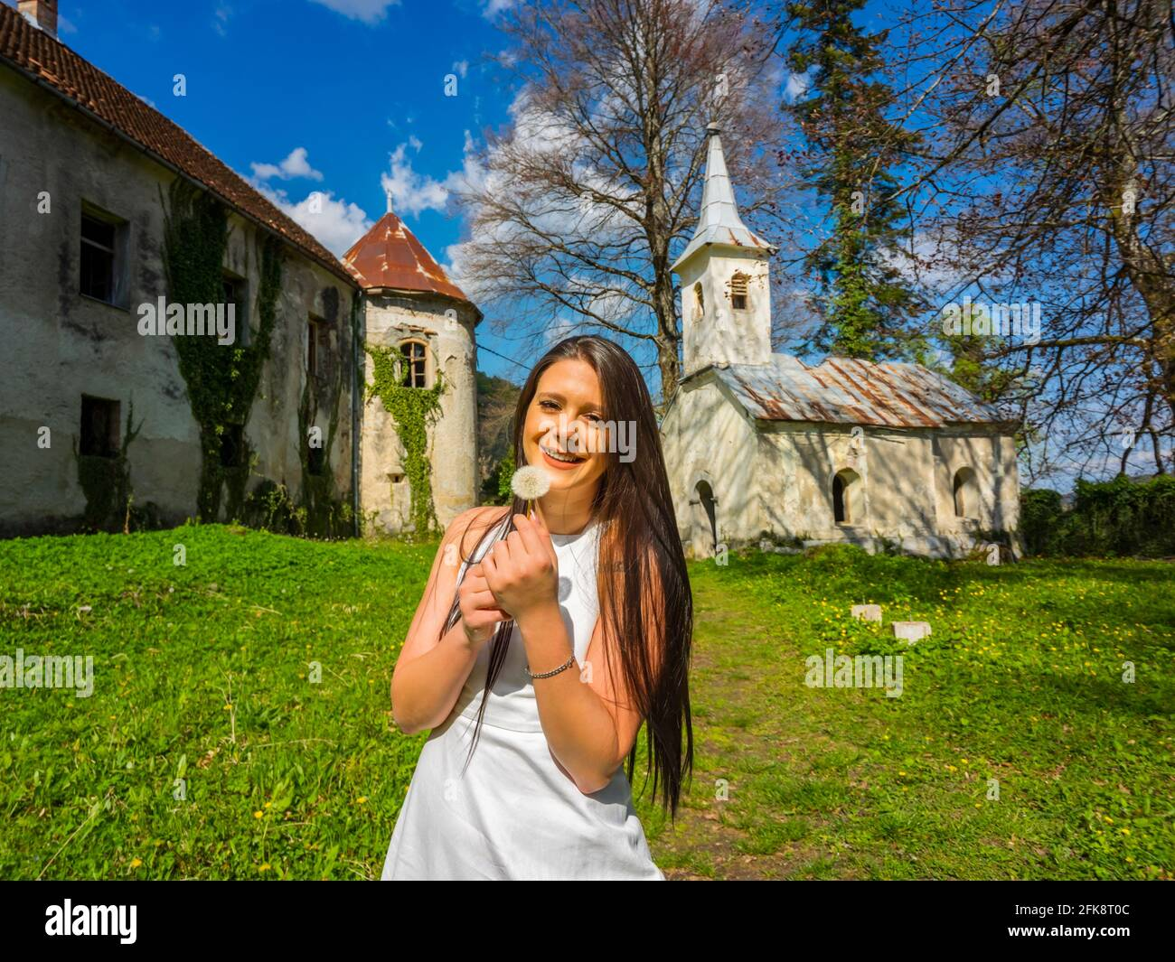 Young woman happy smiling with dandelion flower in hands standing looking at camera in park before abandoned fort building Stock Photo