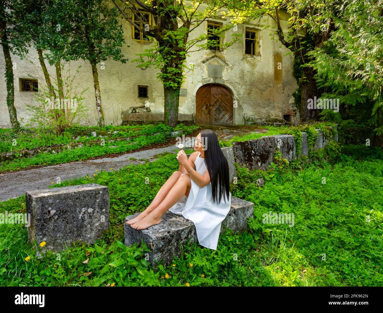 Make a wish young woman sitting barefeet with dandelion flower in hand in park before abandoned fort building Stock Photo