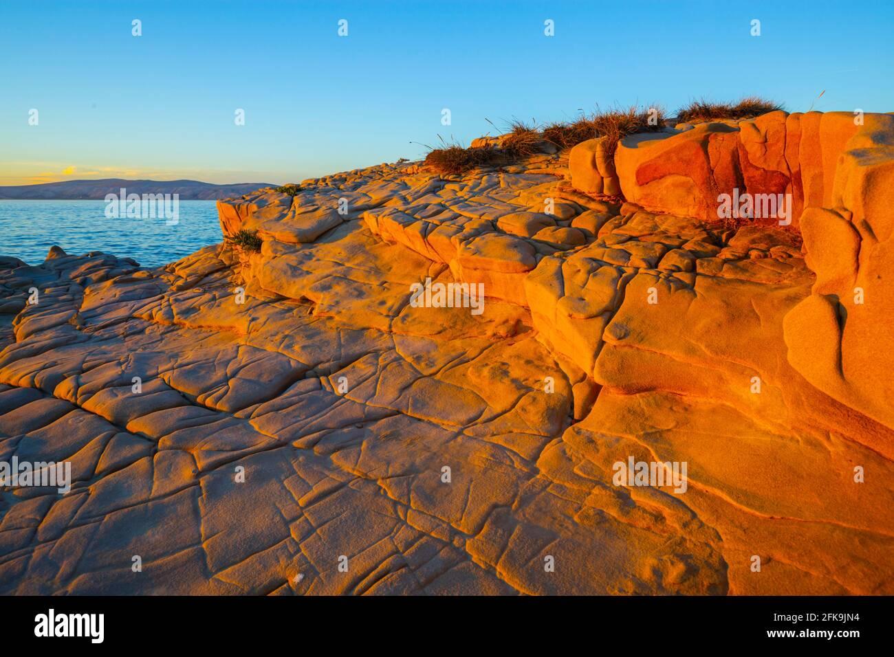 Lopar on Rab island sunset evening wilderness intensive vivid bright Orange-Yellow surface of stone Stock Photo