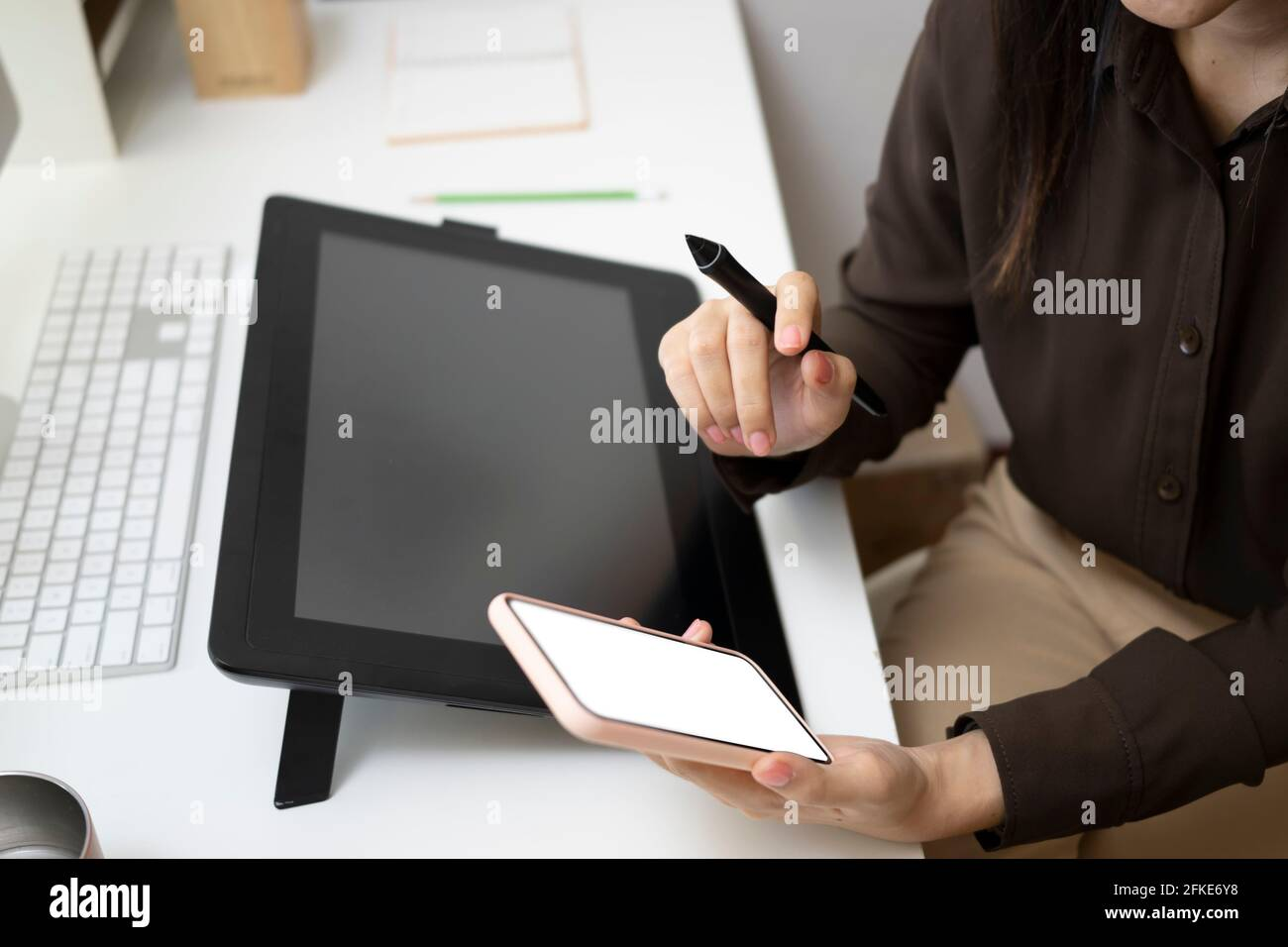 Cropped shot of graphic designer woman sitting at her creative workplace and using mobile phone. Stock Photo