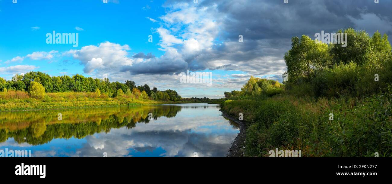 Stormy dramatic sky over the calm lake and green hills during sunset.Beautiful panoramic landscape.Beauty of evening nature. Stock Photo