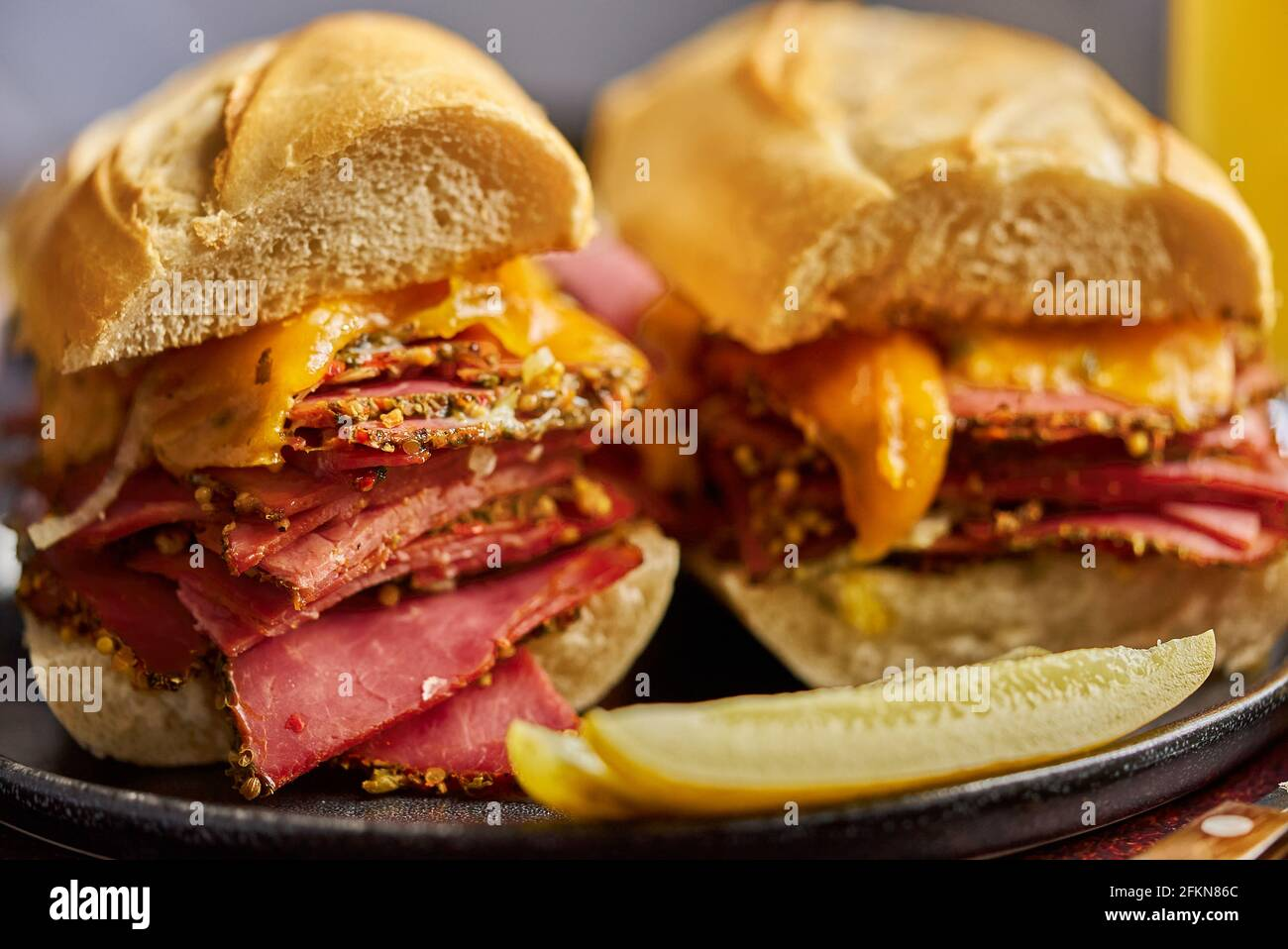 Delicious pastrami meat sandwiches served with glass of beer, pickles, potato chips and sides. Stock Photo