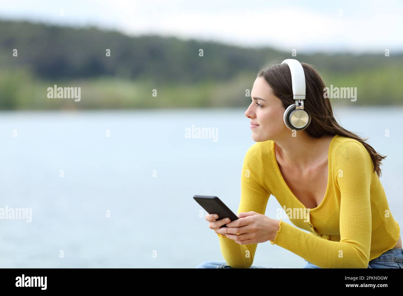 Satisfied woman listening to music with wireless headphones looking away in a lake Stock Photo