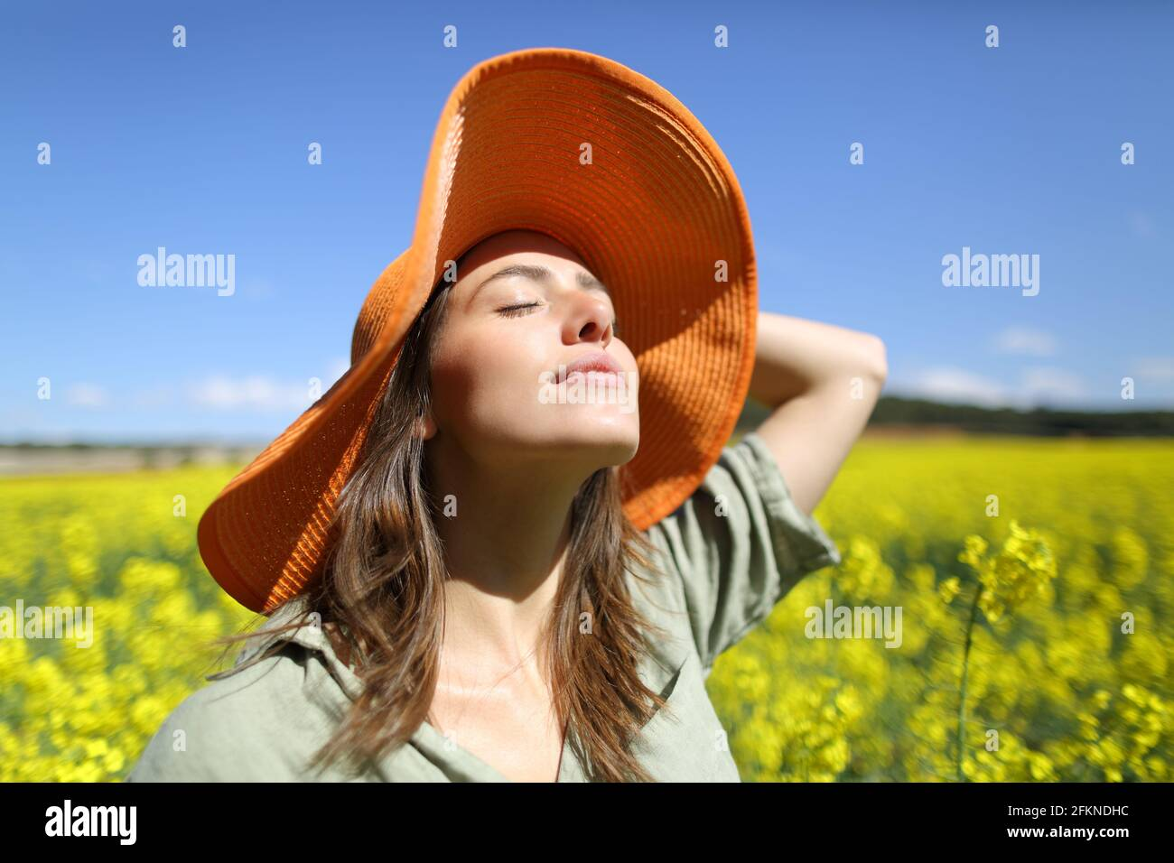 Satisfied woman with orange pamela breathing fresh air in a yellow flowered field Stock Photo