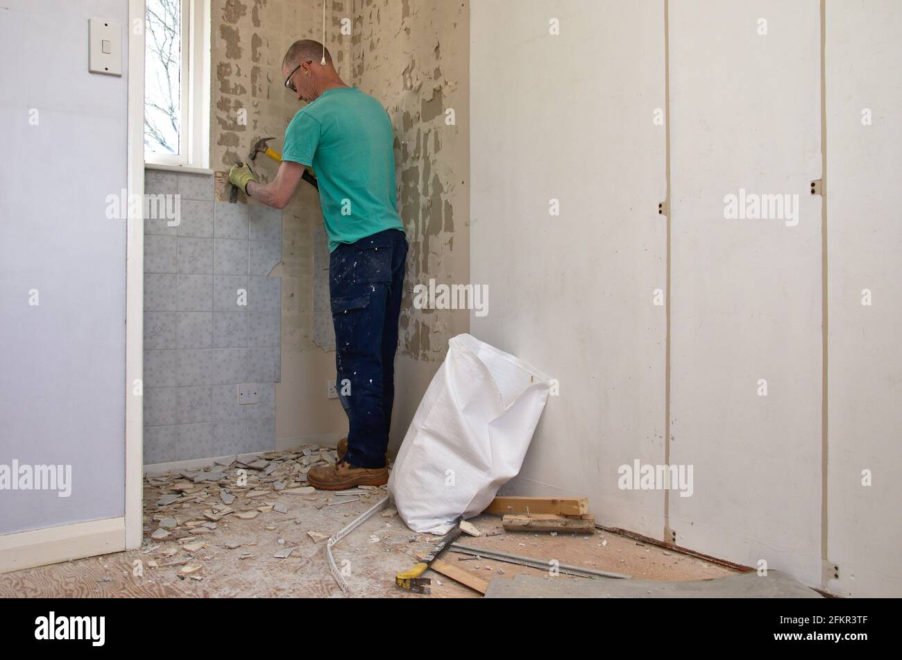 Handyman working on house renovation removing ceramic tiles from a wall. Stock Photo