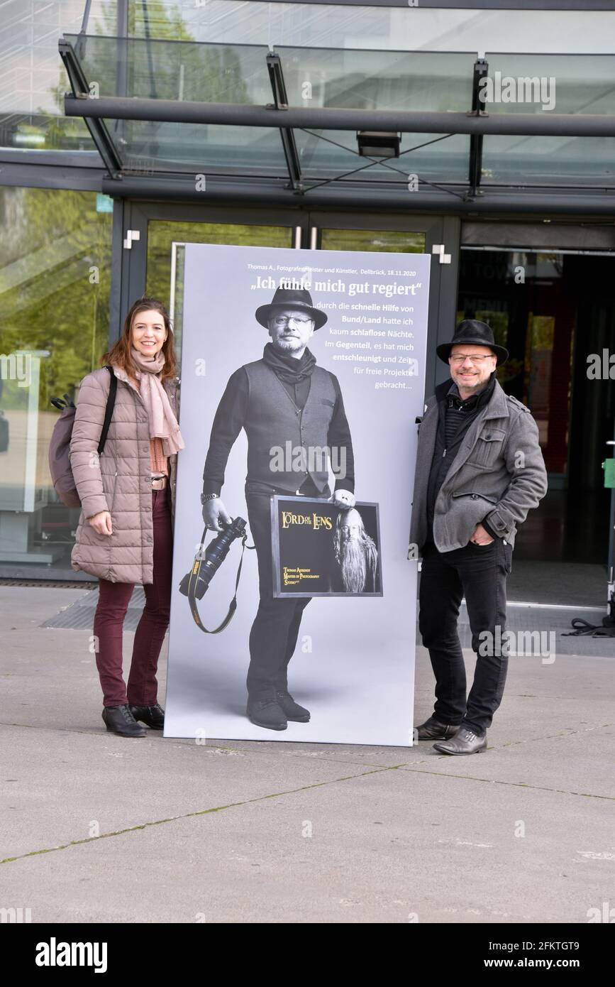 """03 May 2021, North Rhine-Westphalia, Cologne: Artist and photographer Thomas Ahrendt and his wife pose at his opening of the exhibition """"Der Stadt Bestes - Das Gute in der Krise"""". The 70 large-format pictures can now be seen at ground level on the windows of the Lanxess Arena Photo: Horst Galuschka/dpa Stock Photo"""