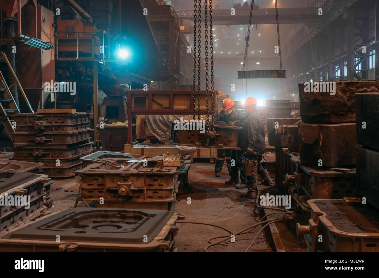 Workers in helmets and face masks works with mold on crane chains after metal casting in steel mill foundry. Stock Photo