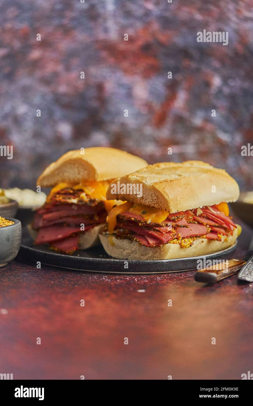 Super deluxe tasty grilled reuben sandwiches with pastrami meat, cheddar cheese Stock Photo