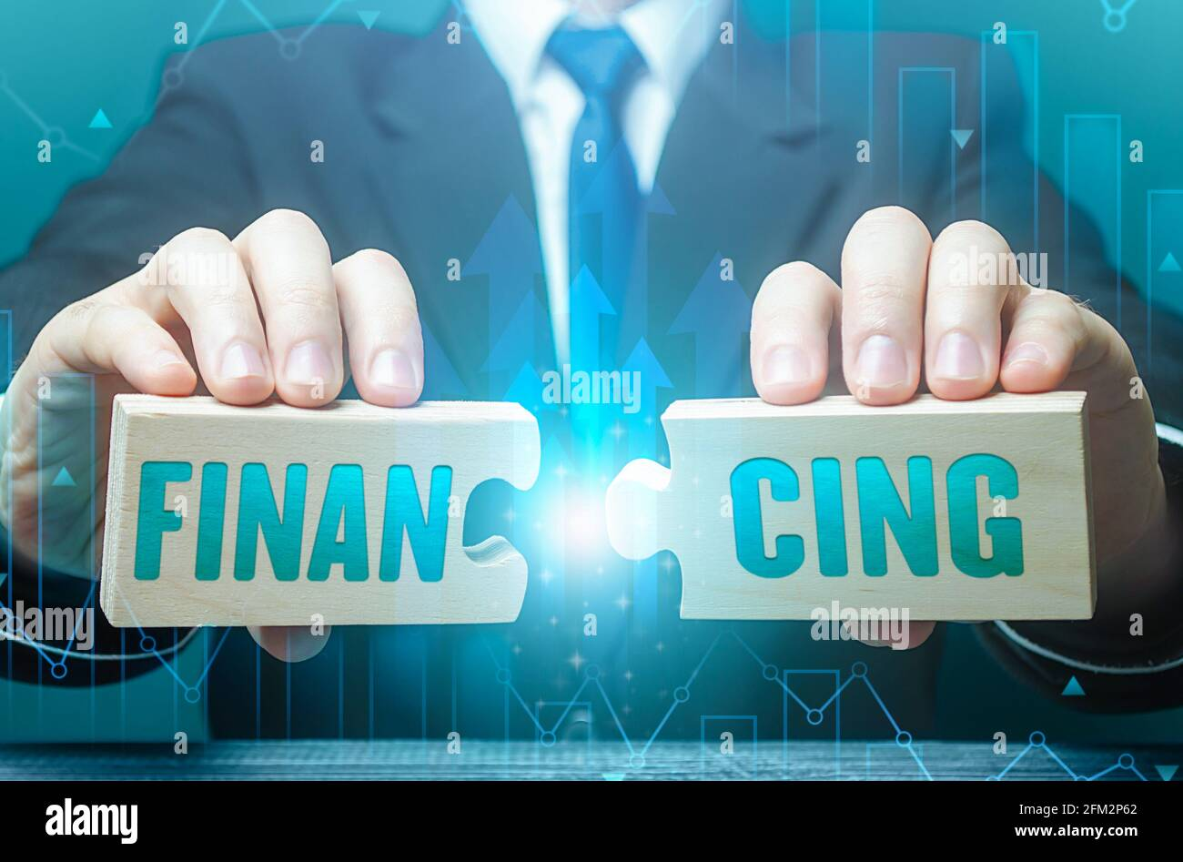 Businessman connects puzzles with the word financing. Investing in a business project, raising funds. Credit, donations, taxes, support grants, saving Stock Photo