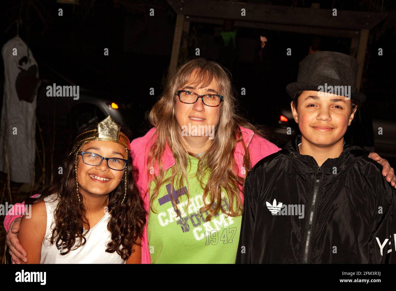 Latino Halloween trick or treaters costumed as a princess and escort in black with their mom. St Paul Minnesota MN USA Stock Photo
