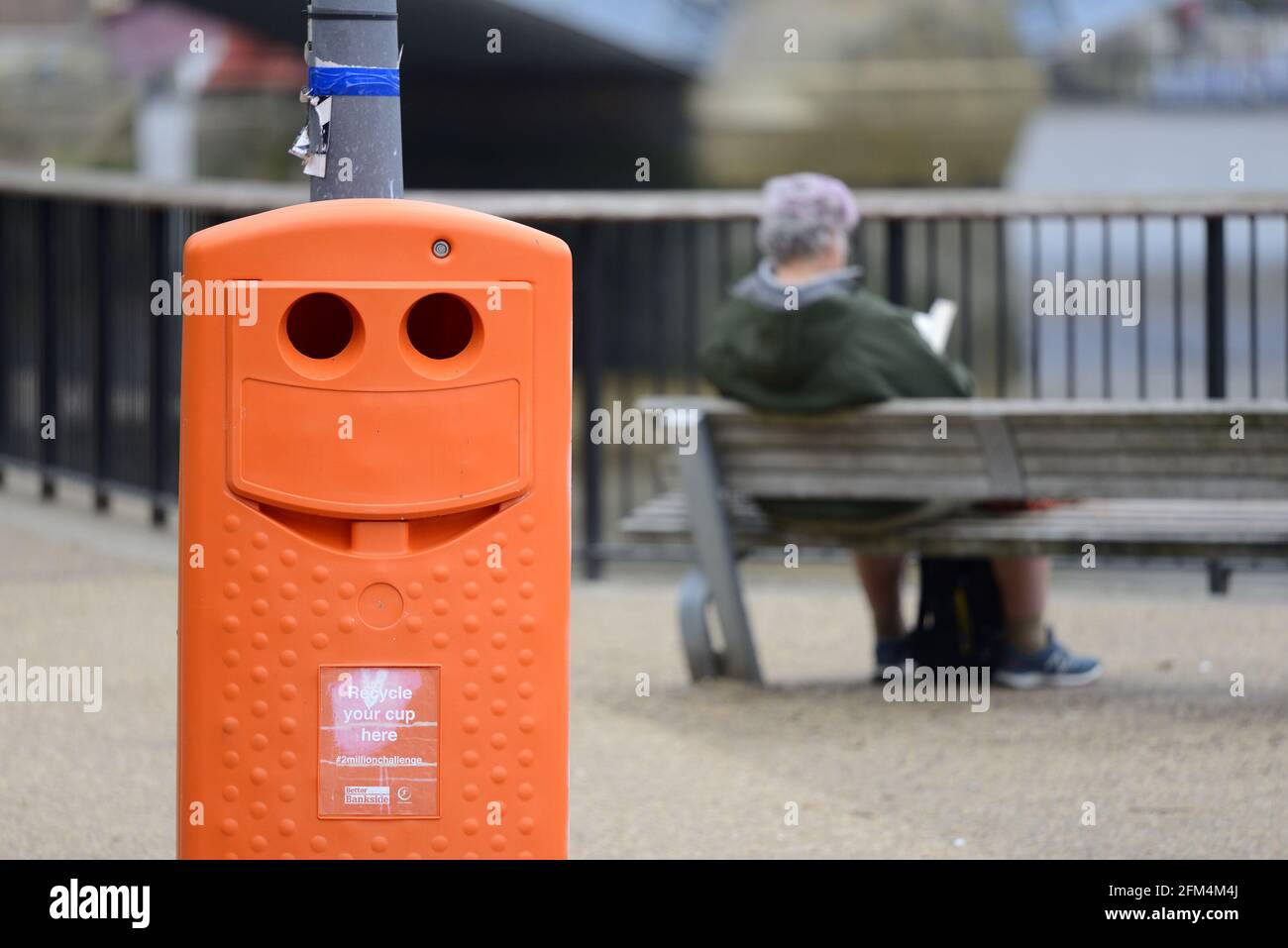 London, England, UK. Smiling recycling bin and a man reading on the South Bank - part of the #2millionchallenge Stock Photo