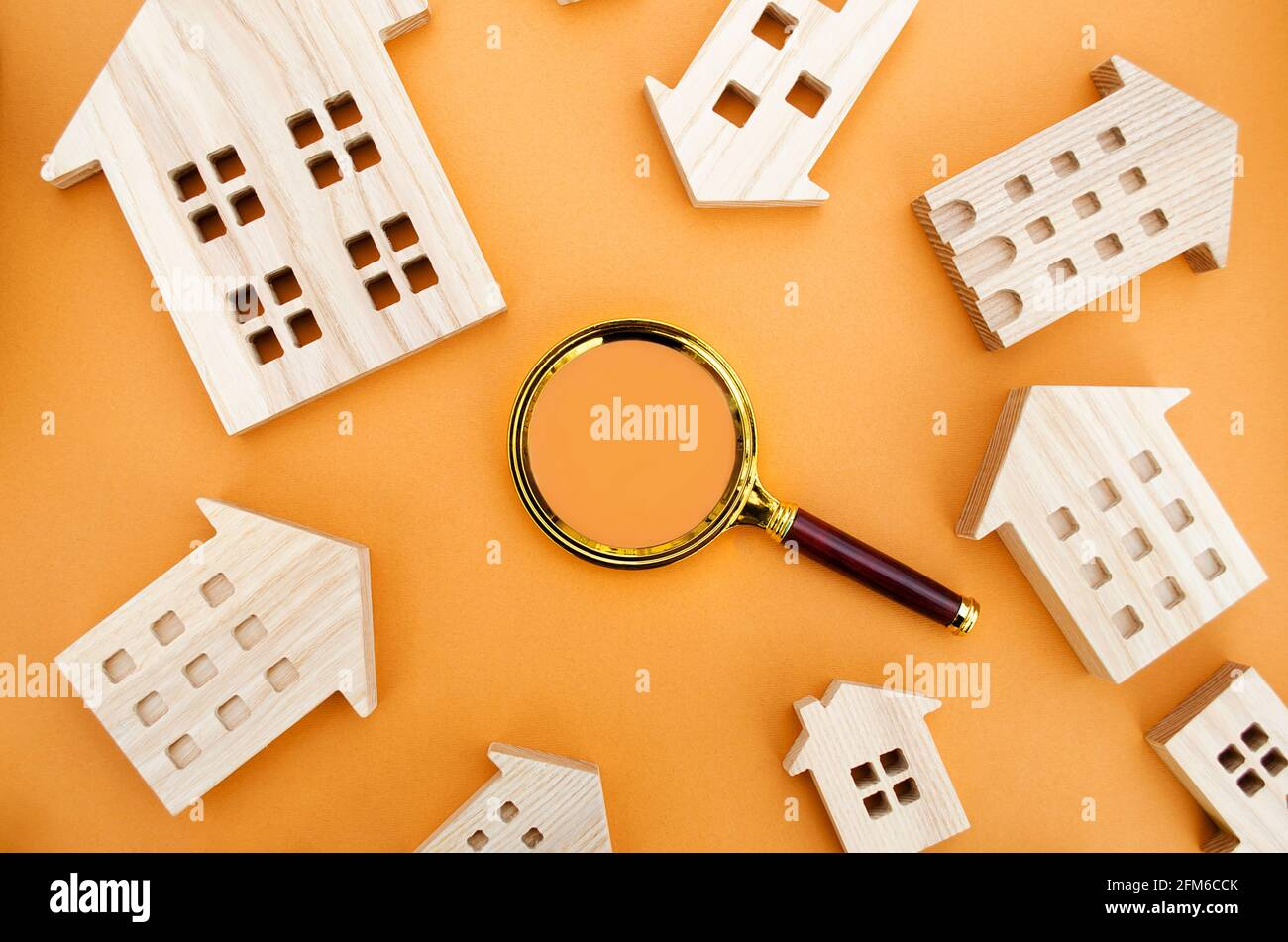 Magnifying glass and wooden houses. House searching concept. Home appraisal. Property valuation. Choice of location for the construction. Search for h Stock Photo