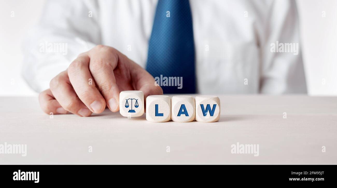 Businessman placing the wooden cubes with the word law. Business legislation or legal rules concept. Stock Photo