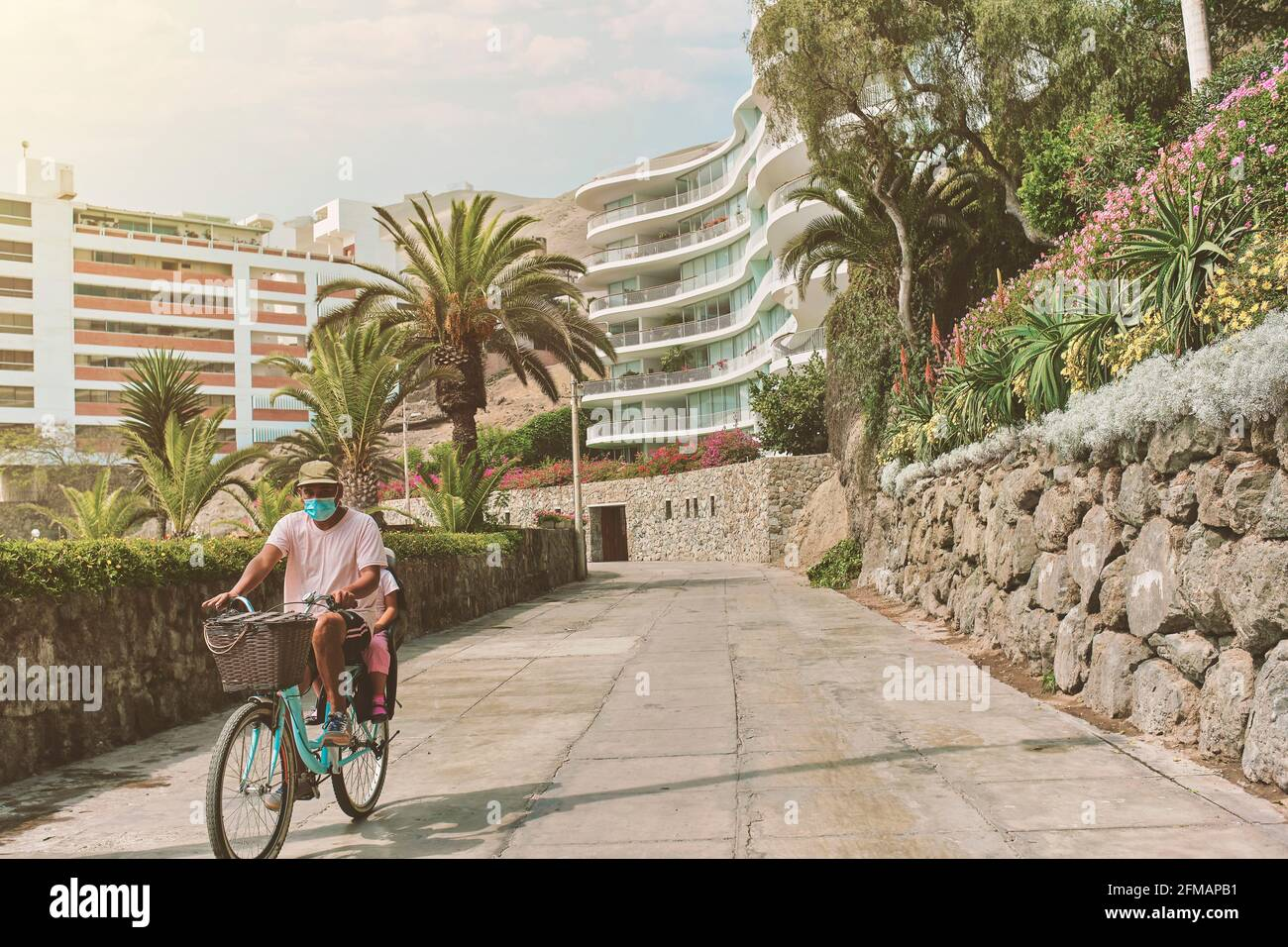 Father with mask on bicycle with his son in a baby seat, morning walk on the boulevard, sunny day. New normal concept Stock Photo