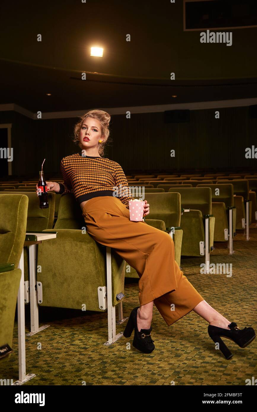 Retro style young blonde woman with coke bottle in cinema room Stock Photo