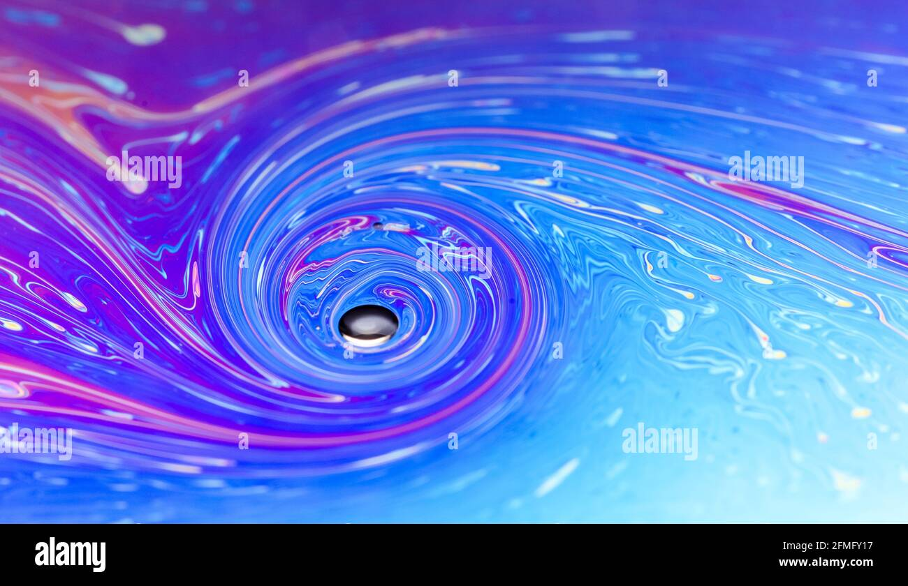 Macro of colorful iridescent flat soap surface with fluid iridescent colors and abstract patterns and shapes, futuristic space art background Stock Photo
