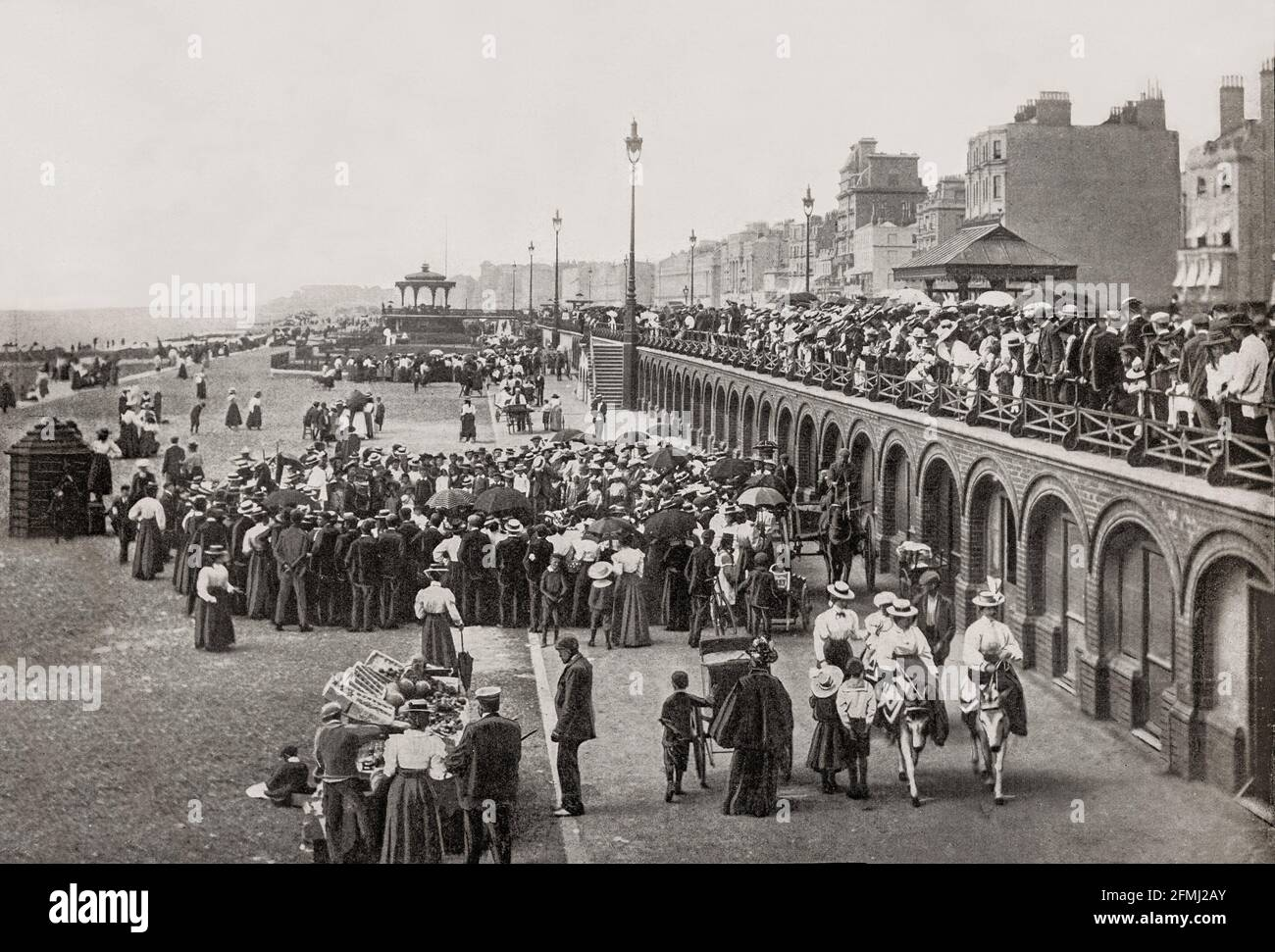 A late 19th Century view of the seafront at Brighton in East Sussex, England. King George IV spent much time in the town and constructed the Royal Pavilion there. The arrival of the London and Brighton Railway in 1841 brought Brighton within the reach of day-trippers from London. Many of the major attractions were built during the Victorian era, such as the Grand Hotel (1864), the West Pier (1866), and the Palace Pier (1899). Stock Photo