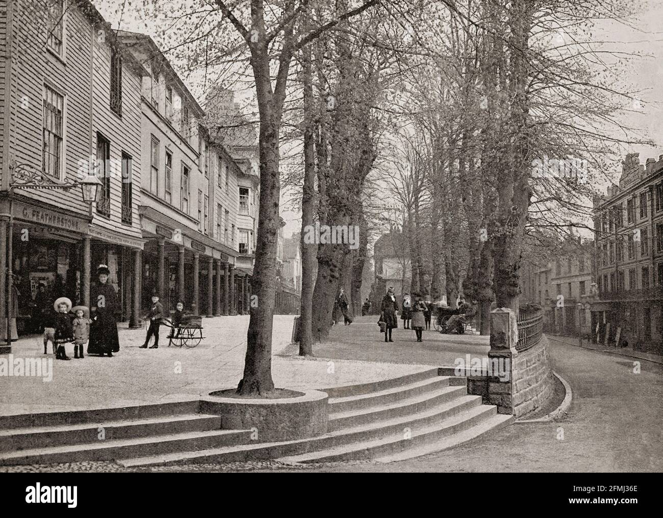 A late 19th Century view of The Pantiles, a Georgian colonnade in the town of Royal Tunbridge Wells, Kent, England constructed in the first part of the 18th century. Formerly known as The Walks and the (Royal) Parade, it leads from the well that gave the town its name. The pantiles used to pave the Upper Walks should not be confused with roofing pantiles. The paving installed there comprised one-inch thick square tiles made from heavy wealden clay, so named because they were shaped in a wooden pan before firing. Stock Photo