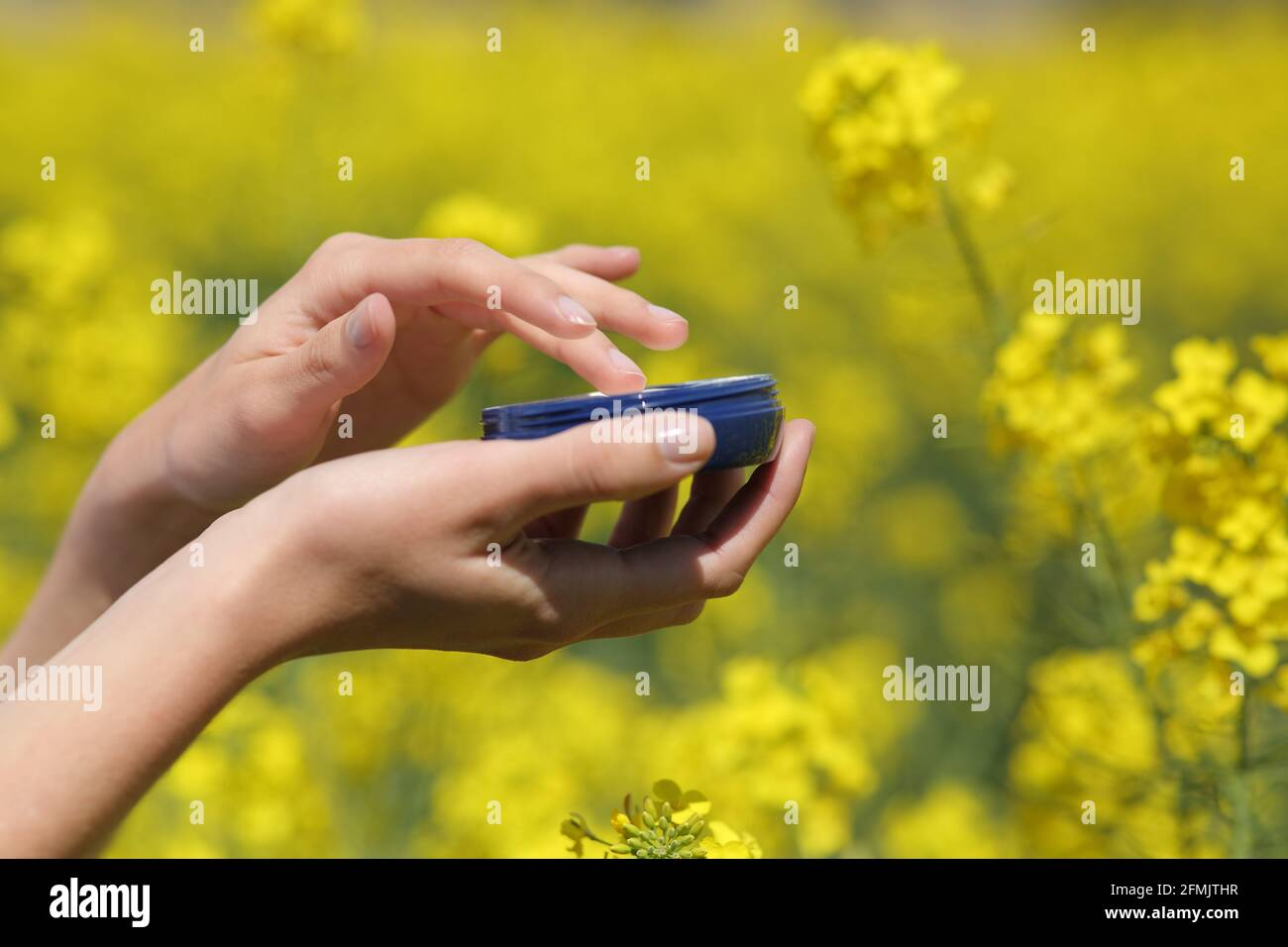 Close up of a woman hand holding moisturizer jar in a yellow field in spring season Stock Photo