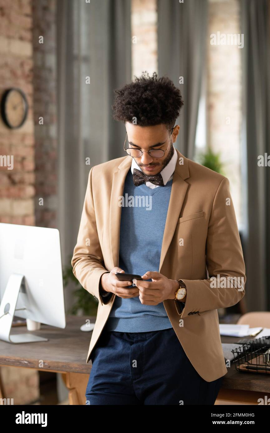 Concentrated young Black man in bow tie standing at office table and checking phone messages Stock Photo