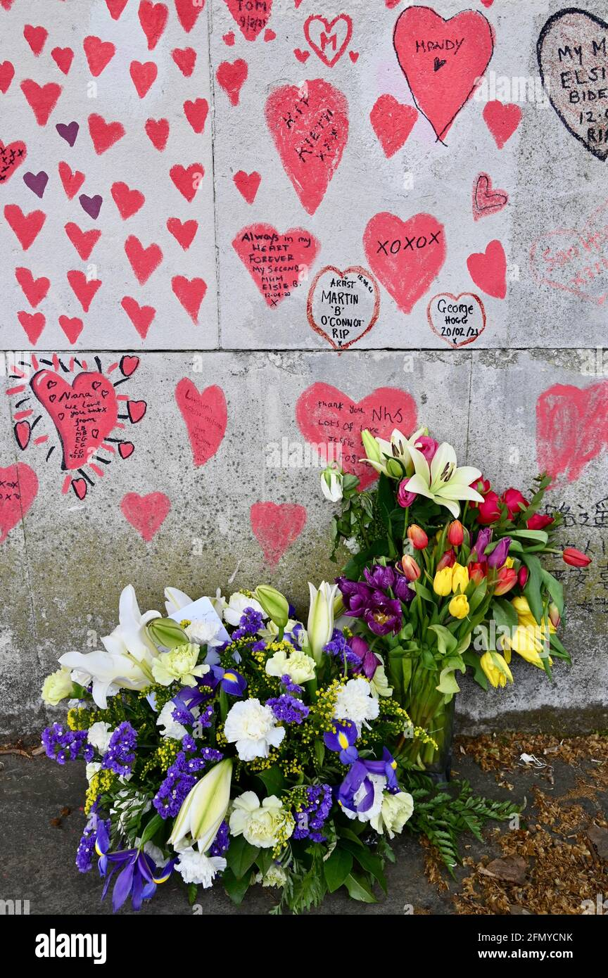 Floral bouquets, National COVID Memorial Wall, a public mural to commemorate victims of the COVID-19 Pandemic.South Bank walkway, Westminster, London. UK Stock Photo