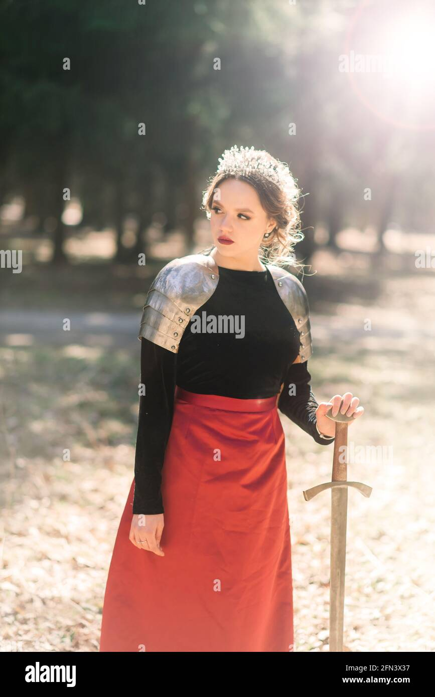 Armed medieval woman warrior in armor posing while standing on background of forest and sunset. Stock Photo