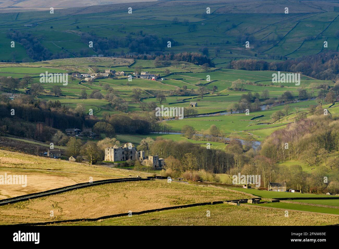 Scenic countryside view of Wharfedale (wide green valley, rolling hills, high upland fells, sunlit Barden Tower ruins) - Yorkshire Dales, England, UK. Stock Photo