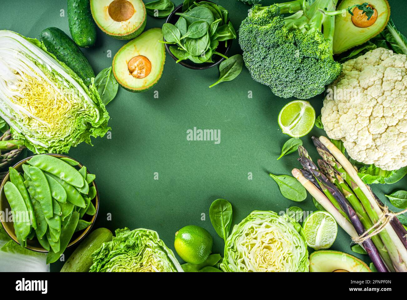 Healthy Diet Spring food background. Assortment of fresh raw organic green vegetables - broccoli, cauliflower, zucchini, cucumbers, asparagus, spinach Stock Photo