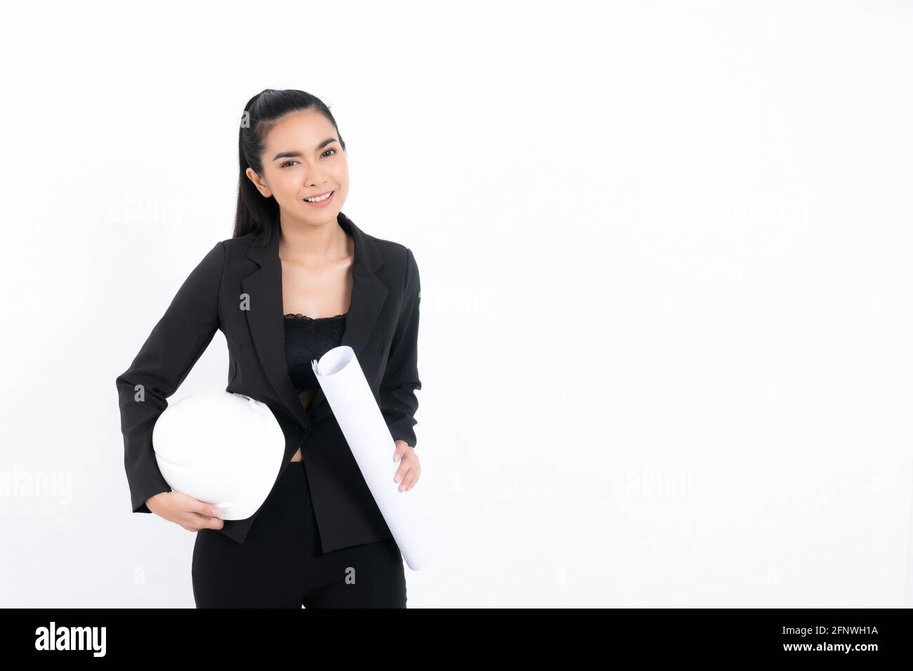 Portrait young engineer woman wearing black suit holding blueprint and white safety-helmet in shot studio isolated on white background. Stock Photo