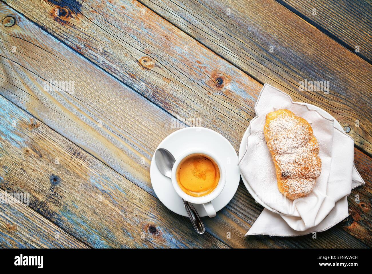View from above. Cup of hot Italian espresso coffee and croissants on a light blue rustic wooden background. Food and drink. Lifestyle. Stock Photo