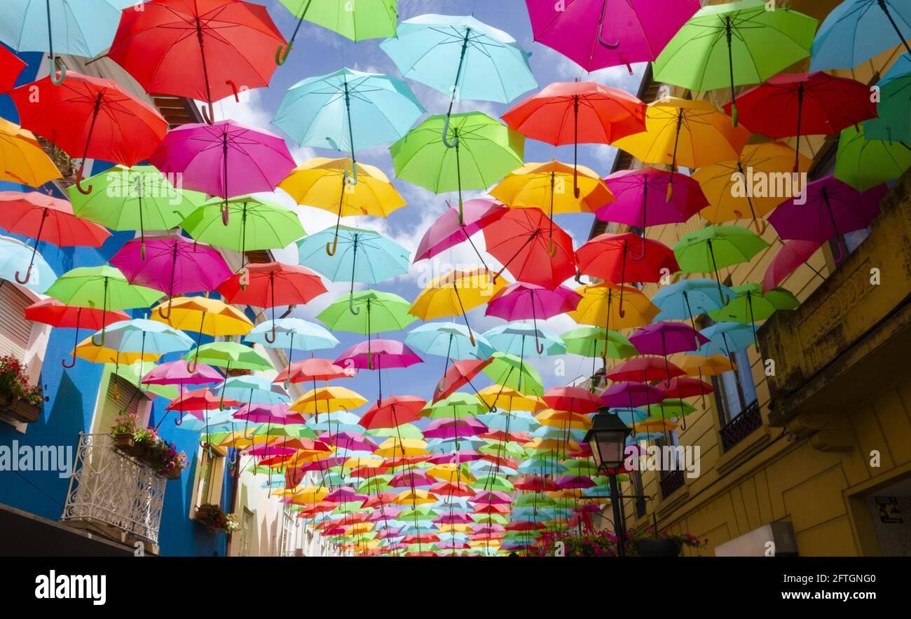 Colorful umbrellas under a blue sky by the Umbrella Sky Project on Rua Luís de Camões Stock Photo